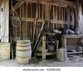 Antique farm tools on the floor and hanging on the wall of an old wood barn.