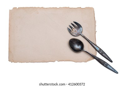 antique flatware lying on a sheet of aged paper menu