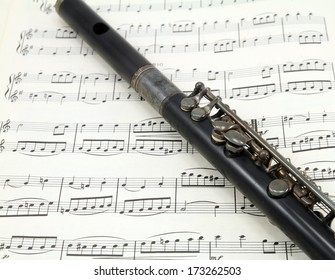 An antique flute on a sheet of old music.