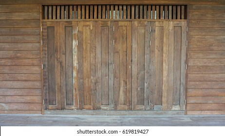 Antique folding doors at wooden home with wind channel on top, brown texture with line and structured pattern, rural house, the vertical folding doors closed, wall stripped in horizontal line