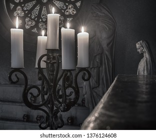Antique forged candelabrum with burning candles, stained glass and a small statue in black and white format