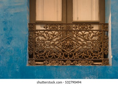 Antique forged iron window grille at a blue facade in Tarragona, Catalonia, Spain. Streets of the beautiful medieval old city of Tarragon, Tarraco for the ancient Roman empire.