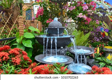 Antique fountain at garden. Blue water flowing from stone fountain. Design of antique fountain