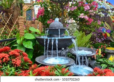 Antique fountain at garden. Blue water flowing from stone fountain. Design of antique fountain