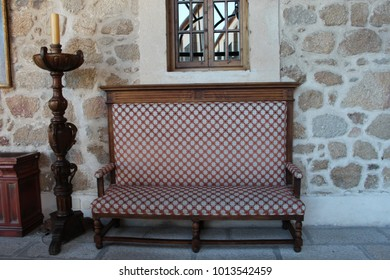 Antique furniture: vintage sofa and a candle with wooden support with stone wall in the background