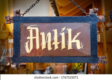 antique in german text on old board in German store. Antik Metal old board in shop. Antik Metal old board in shop. Vintage plate sign hanging with metal chains
