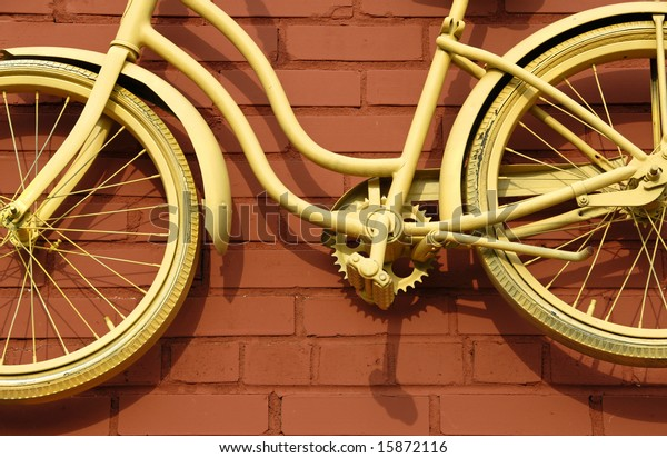 Antique Girls Bicycle Painted Yellow against Rust Colored Brick Wall