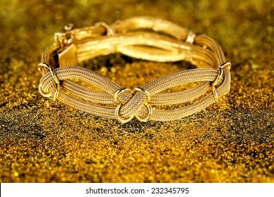 antique gold bracelet on sparkling surface