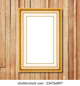 Antique gold frame on wooden wall;. Empty  picture frame on wooden wall.