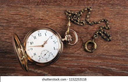 An antique gold pocket watch lies on a wooden table top view