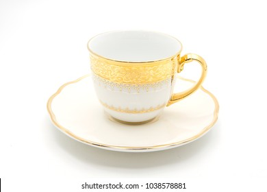 Antique gold tea cup with saucer on white background
