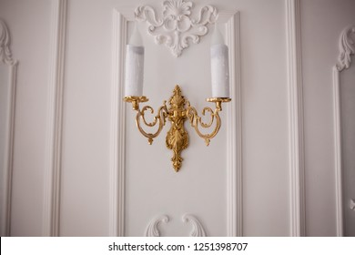 antique golden candlestick on white wall. Retro copper candlestick hanging on the wall. Vintage golden candlestick with light bulbs. Gold wall candle holder on a white background. closeup photo