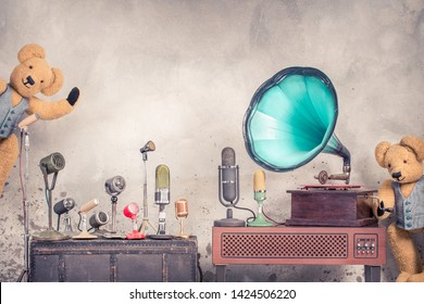 Antique gramophone phonograph turntable with mint blue horn, old retro microphones, two Teddy Bear toys front loft aged concrete wall background. Nostalgia music concept. Vintage style filtered photo