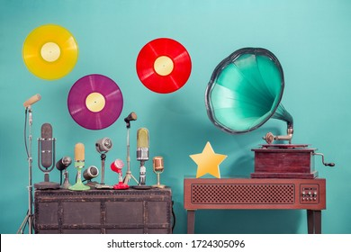Antique gramophone phonograph turntable, old retro microphones, flying LP vinyl record discs, golden award star front mint blue background. Nostalgic music concept. Vintage style filtered photo
