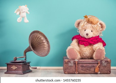 Antique gramophone phonograph turntable, Teddy Bear toy sitting on old luggage and flying bear with angel's wings front mint blue wall background. Nostalgia music concept. Vintage style filtered photo
