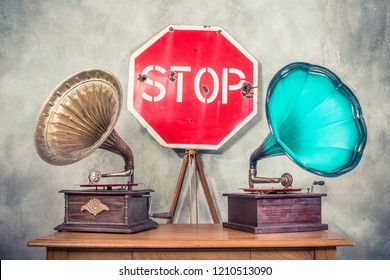 Antique gramophone phonograph turntables with brass and turquoise horns on wooden table and retro aged STOP road sign front concrete wall background. Vintage old style filtered conceptual photo
