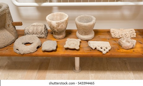 Antique Greek clay pots and stucco moulding fragments on desk