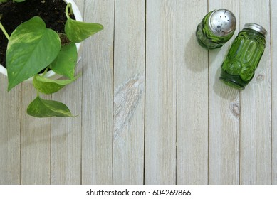 Antique green glass salt and pepper shakers on a pale slatted wood surface or desk from a top down ariel view perspective and a potted house plant vine in the corner.
