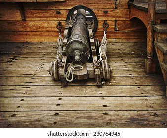 Antique gun ready to fire on antique vessel on grunge texture