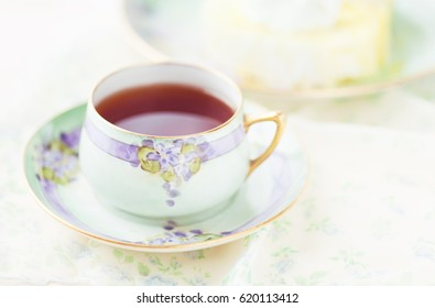 Antique, hand painted cup and saucer with red rooibos tea and lemon creme roll dessert in background.