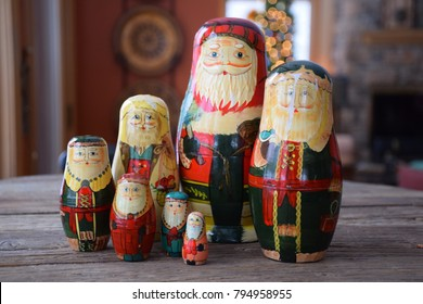 Antique hand painted set of traditional Russian matryoshka nesting dolls on wooden table at Christmas with Christmas tree and fireplace in background