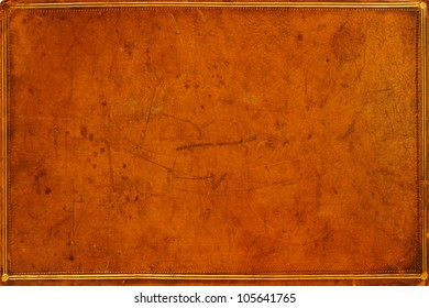 Antique, honey-coloured, leather-bound book cover with gilded banding and tooling . Textured, distressed and marked from ages of use. Grunge background.