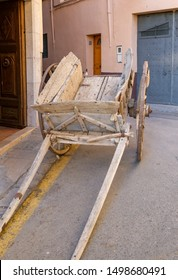 Antique horse drawn wooden cart near a museum in a modern city. Installation for a traditional medieval festival in Spanish town.