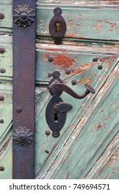 antique iron door handle on a wooden door