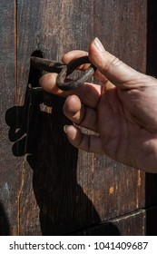 antique iron key in the door lock and hand turns the key