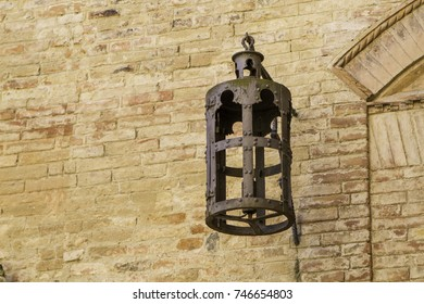 Antique iron street lamp on stone wall of a middle ages house in Tuscany, Italy.