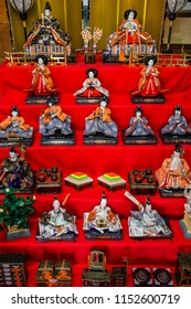 Antique Japanese dolls clothed in colorful kimonos represent an ancient king and queen and their royal court during the Japan Dolls Festival ('Hinamatsuri').