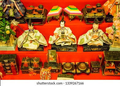 Antique Japanese dolls representing an ancient royal court and miniature furniture are displayed on shelves covered with bright red cloth for the Dolls Festival ('Hinamatsuri') in Japan.