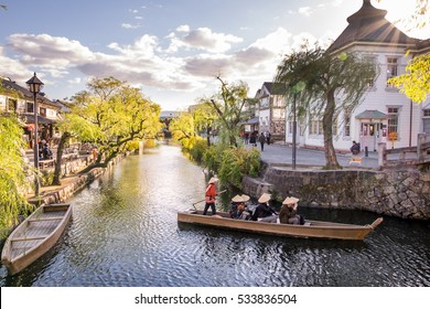 Antique Japanese rowing boats with tourists inside ,running pass lake city japan at Kurashiki Bikan Historical Quarter, the Traditional Boat Tour of Kurashiki Canal Sailing through the center of town