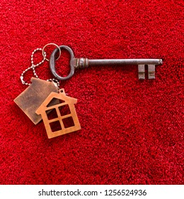 Antique key with keychain in the form of a house on the red carpet