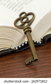 Antique key on opened book page