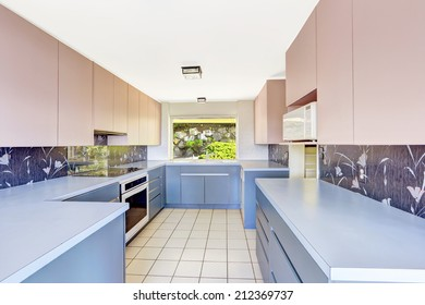 Antique Kitchen room with blue and pink storage combination, decorated back splash. Unique modern old home build in 1952.