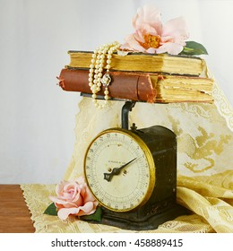 Antique kitchen scale with stacked vintage books draped with old lace. Pink silk roses and pearls lay on top and beside. White linen background. Vintage filter applied, Square composition