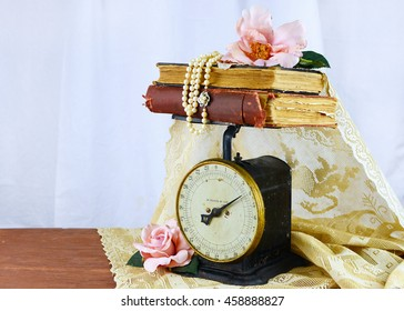 Antique kitchen scale with vintage books stacked on top all draped with old lace. Pink silk roses and pearls lay on top and beside. Old romantic vibe. White linen background. Copy space.