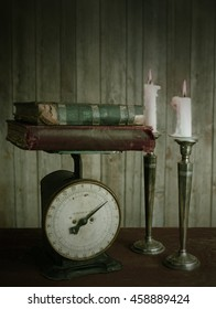 Antique kitchen scale with worn vintage books stacked on top. Two white candles on silver candlesticks are burning. Wooden background and vintage filter for rustic vibe. Low key lighting from right
