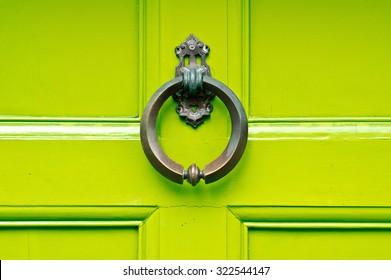 An antique knocker on a lime green wooden door