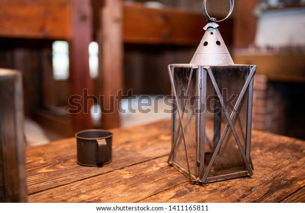 An Antique Lantern and cup on a scratched wooden table with a blurry interior background.