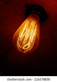 Antique light bulb, filament glowing, screwed in a socket