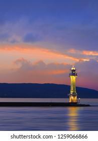 Antique lighthouse at multicolored dramatic sunset, Lake Geneva, Switzerland.