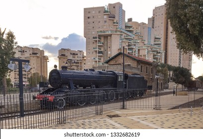 an antique locomotive and railway terminal surrounded by modern high rise apartment buildings in beer sheva in israel