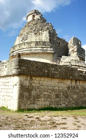 Antique maya observatory over blue sky and green grass