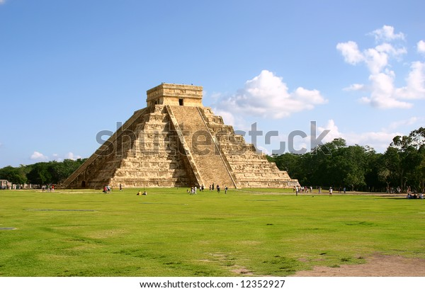 Antique mayan pyramid on green field over blue sky