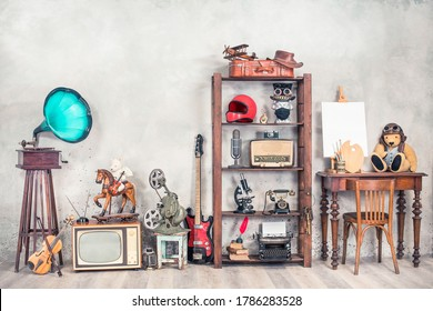 Antique media devices, writers tools, gramophone, film projector, old Teddy Bear toys and white canvas blank on easel, violin and guitar front concrete wall background. Vintage style filtered photo