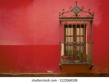 Antique medieval window with rusty iron bars and Red Pear orange wall in old Santa cruz quarter in Seville, Spain