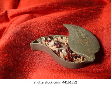 antique metal box of Indian mouth freshener mixture on glossy red silk