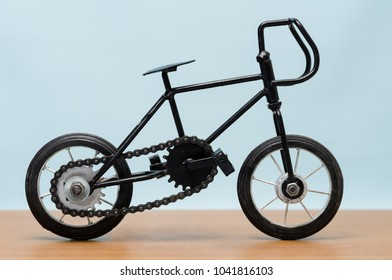 Antique miniature bicycle. Side view of the bicycle on the wooden table.